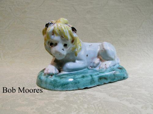18th century faience model of a recumbent lion 16cm long